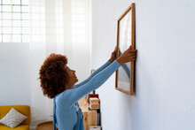Redhead Woman Installing Photo Frame On White Wall