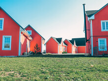 Norwegian Village, Red Wooden Houses With White Edging, White Windows, A Long Pipe Sticking Out Of The House, Green Grass, Clear Blue Sky