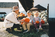 Mother With Children Are Choosing Pumpkin In Farm Market. Woman And Little Kids Playing On Fall Walk At Countryside. Thanksgiving Holiday And Halloween. Happy Family At Autumn Season.