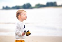 Cute Boy With Toy Car At Beach