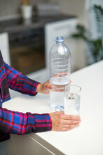 Frame Image Of A Female Hand Holding Drinking Water Bottle And Pouring Water Into Glass On Table On Blurred Kitchen Background.