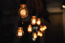 Lamp Bulbs Hanging On A Dark Background.