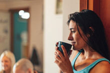 Side View Of Young Attractive Woman Holding A Cup Of Tea In Her Hands - Girl Relaxes At The Youth Hostel - Student Drinks Coffee In A Room With Flatmates