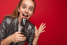 Shot Of Pretty Happy Positive Brunette Little Girl Wearing Fashionable Shine Dress Standing Isolated Over Red Background Wall Singing Tha Song Into The Silver Microphone Looking At Camera
