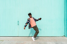 Ecstatic Man Holding Smart Phone While Dancing In Front Of Turquoise Wall