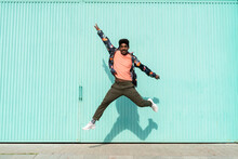 Cheerful Man Dancing In Front Of Turquoise Wall During Sunny Day