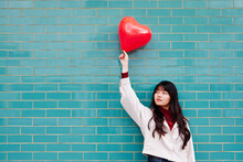 Young Woman Looking Away While Holding Red Heart Shape Balloon In Front Of Brick Wall