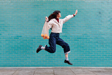 Excited Young Woman Jumping While Holding Mesh Bag By Turquoise Brick Wall