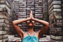 Young Woman Doing Yoga In Front Of Stone Wall