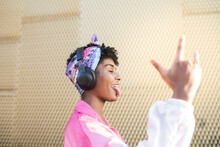 Carefree Woman Making Horn Sign While Listening Music On Headphones