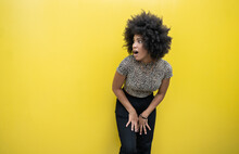 Shocked Afro Woman With Mouth Open In Front Of Yellow Wall