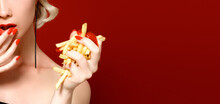 Unhealthy Eating. Junk Food Concept. Portrait Of Fashionable Young Woman Holding Eating Fried Potato Fries, Chips In Her Hand And Posing Over Red Background. Close Up. Copy Space. Studio Shot