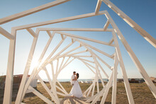 Man And Woman Posing. Geometric Wooden Structures. The Bride And Groom.