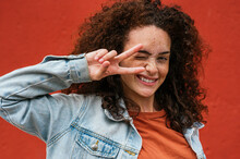 Playful Young Woman Showing Peace Sign While Winking In Front Of Red Wall