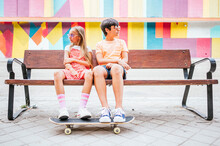 Friends With Skateboard Sitting Together On Bench