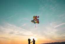 Girls In Silhouette Looking At Helium Balloons Flying In Air During Sunset