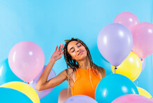 Braided Woman With Eyes Closed Sitting Amidst Multi Colored Balloons Over Blue Background