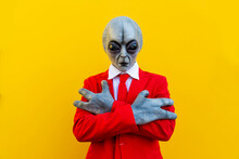 Portrait Of Man Wearing Alien Costume And Bright Red Suit Standing With Crossed Arms