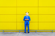 Man Wearing Vibrant Blue Suit And Rodent Mask Standing In Front Of Yellow Wall