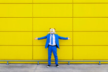 Man Wearing Vibrant Blue Suit And Rodent Mask Standing In Front Of Yellow Wall With Outstretched Arms