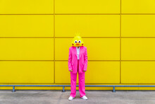 Woman Wearing Vibrant Pink Suit And Bird Mask Standing In Front Of Yellow Wall