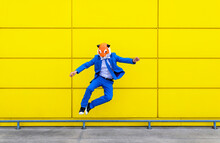 Man Wearing Vibrant Blue Suit And Tiger Mask Jumping Against Yellow Wall