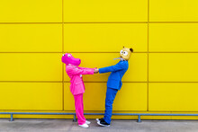 Man And Woman Wearing Vibrant Suits And Animal Masks Holding Hands In Front Of Yellow Wall