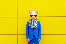 Man Wearing Vibrant Blue Suit, Pig Mask And Large Golden Chain Standing In Front Of Yellow Wall