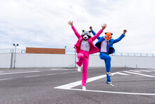 Man And Woman Wearing Vibrant Suits And Animal Masks Jumping Side By Side In Empty Parking Lot
