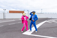 Man And Woman Wearing Vibrant Suits And Animal Masks Posing Side By Side In Empty Parking Lot