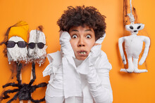 Scared Young African American Woman Stares With Horrified Expression At Camera Grabs Face Shakes From Fear Cannot Believe Her Eyes Poses Around Halloween Decorations Against Orange Background