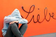 Sad Teenage Boy Sitting In Front German Word For Love On Orange Wall