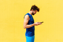 Mid Adult Man Text Messaging Through Smart Phone While Standing By Yellow Wall