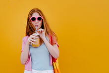 Woman Drinking Juice From Mason Jar In Front Of Yellow Wall