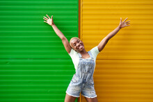 Cheerful Young Woman With Arms Raised In Front Of Two Tone Wall