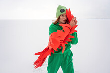 Smiling Woman In Bird Costume Hiding Face With Wings While Standing On Snow Against Sky