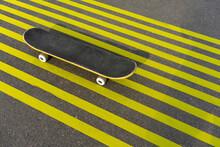 Skateboard On Striped Yellow Road Marking