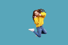 Full Length Portrait Of Happy Charming Little Girl Jumping Up High And Showing Thumb Up To Camera, Wearing Yellow Casual Style Sweater. Indoor Studio Shot Isolated On Blue Background.