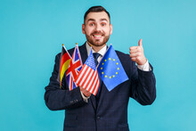 Portrait Of Happy Bearded Businessman Wearing Official Style Suit Holding Flags Of Germany, USA, Great Britain And Europe Union, Showing Thumb Up. Indoor Studio Shot Isolated On Blue Background.
