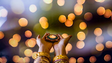 Happy Diwali - Woman Hands With Henna Holding Lit Candle Isolated On Dark Background. Clay Diya Lamps Lit During Dipavali, Hindu Festival Of Lights Celebration.