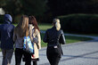 kobiety, dziewczyny i mężczyzna spacerują deptakiem w parku.