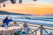 Seaside Landscape - Tourist Photographs The Sunrise Over The Sea With His Smartphone, City Embankment Of Varna, On The Black Sea Coast Of Bulgaria