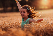 One Little Girl Chasing In The Wheat Field. Fun At The Countryside On The Agricultural Field During Sunset.