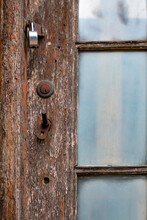 Deeply Worn Wooden Door With Rusty Keyhole And Glazed Window Panes