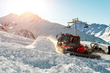 Red Modern Snowcat Ratrack With Snowplow Snow Grooming Machine Preparing Ski Slope Piste Hill At Alpine Skiing Winter Resort Ischgl In Austria. Heavy Machinery Mountain Equipment Track Vehicle