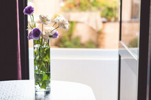 White And Purple Flowers Stand In A Vase Of Water On The Table. There Is A Beautiful View From The Window.