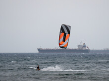 Kitesurfing During A Windy Day With A Very Rough Sea And Industrial Boat In The Background