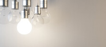 Glowing Lightbulb On Blurry Panoramic Concrete Wall Background. Idea, Innovation, Solution And Invention Concept. Mock Up, 3D Rendering.
