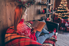Photo Of Dreamy Charming Young Woman Dressed Red Sweater Reading New Year Fairytales Smiling Indoors Room Home House