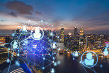 Glowing Social Media Icons On Night Panoramic City View Of Singapore, Asia. The Concept Of Networking And Establishing New Connections Between People In Businesses. Double Exposure.